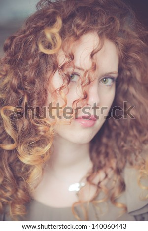Redhead Beauty with curly hair and green eyes - stock photo
