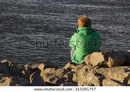 redhead boy by river - stock photo