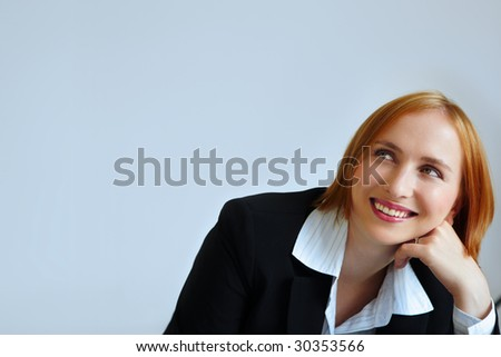 redhead businesswoman smiling. not isolated. - stock photo