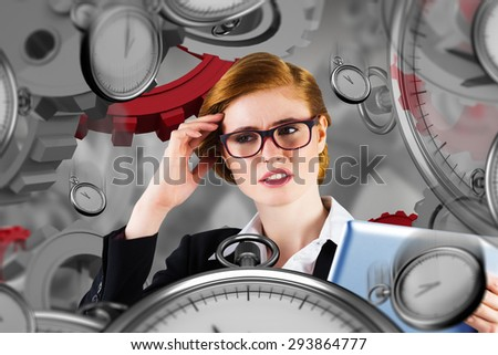 Redhead businesswoman using her tablet pc against grey vignette - stock photo