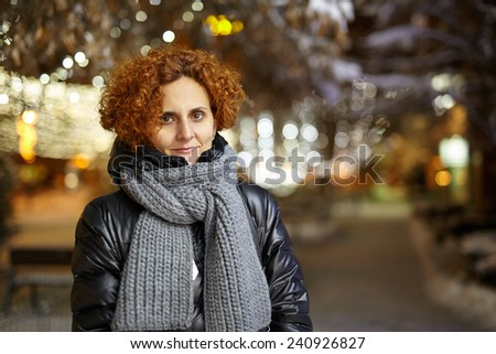 Redhead curly hair caucasian woman outdoor with winter city lights behind - stock photo