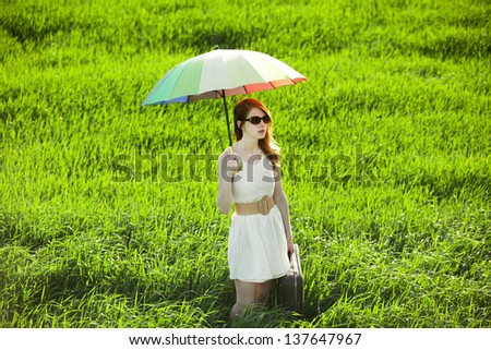 Redhead enchantress with umbrella and suitcase at spring countryside - stock photo