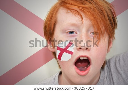 redhead fan boy with alabama state flag painted on his face.  - stock photo