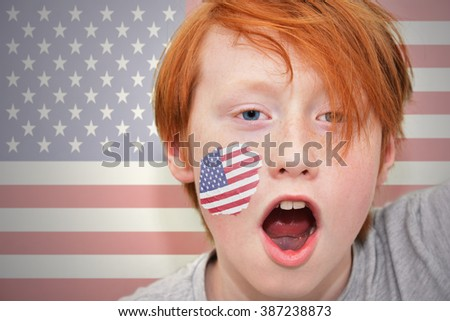 redhead fan boy with american flag painted on his face.  - stock photo