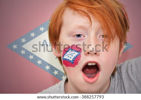 redhead fan boy with arkansas state flag painted on his face.  - stock photo