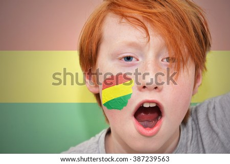 redhead fan boy with bolivian flag painted on his face. on the bolivian  flag background - stock photo