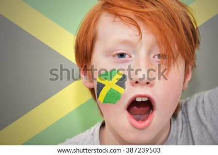 redhead fan boy with jamaican flag painted on his face.  - stock photo