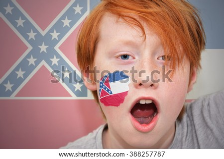redhead fan boy with mississippi state flag painted on his face.  - stock photo