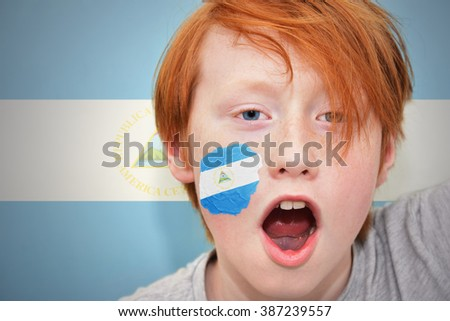 redhead fan boy with nicaraguan flag painted on his face. on the nicaraguan  flag background - stock photo