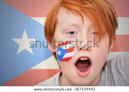 redhead fan boy with puerto rican flag painted on his face.  - stock photo