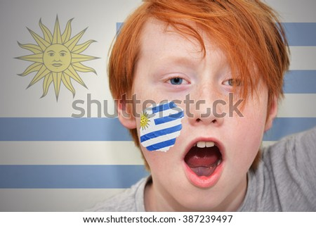 redhead fan boy with uruguayan flag painted on his face.  - stock photo