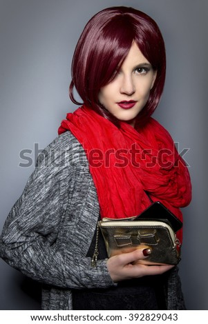 Redhead fashion model holding a stylish cell phone purse accessory.  The purse is a case for the mobile phone. - stock photo