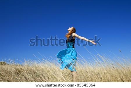 Redhead girl at windy field - stock photo