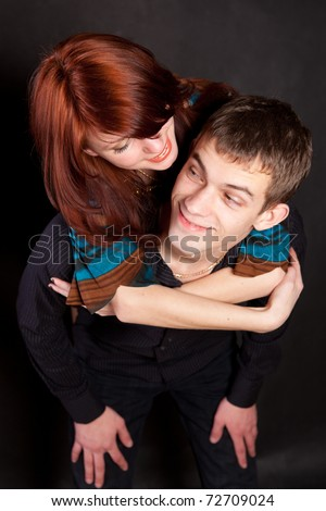 Redhead girl hung guy on the neck - stock photo