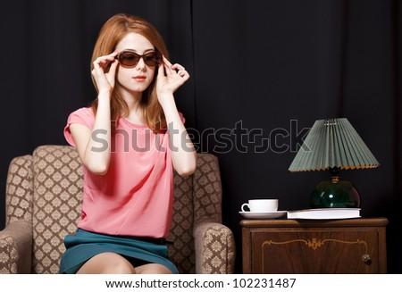 Redhead girl in armchair. 70s - stock photo