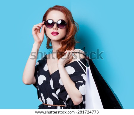 Redhead girl in black dress with shopping bags on blue background - stock photo