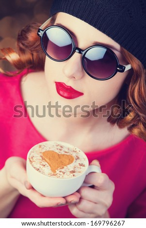 Redhead girl in glasses with cup of coffee. - stock photo