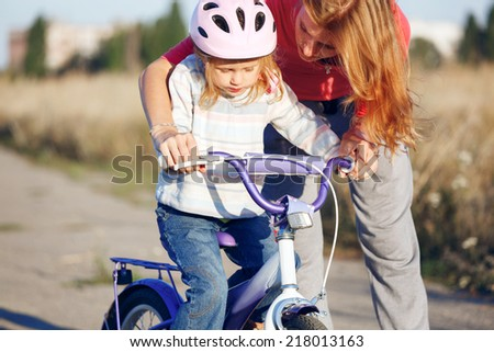 Redhead girl in helmet learning riding bike. - stock photo