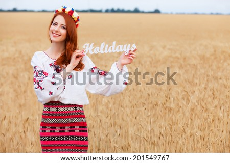 Redhead girl in nationac ukrainian clothes with wooden word Holidays on the wheat field. - stock photo