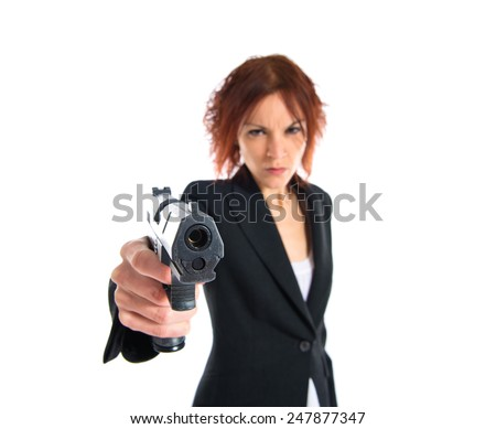Redhead girl shooting with a pistol  - stock photo