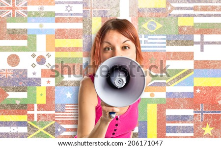 Redhead girl shouting with a megaphone over white background  - stock photo