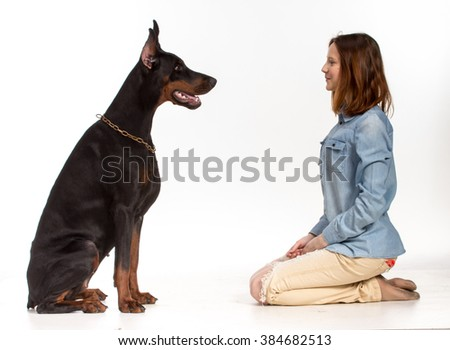 Redhead girl sitting on her knees in front of a large black doberman  dog, isolated on white - stock photo