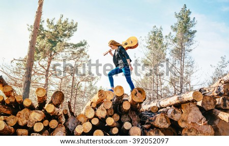 Redhead girl the guitarist goes on fallen trees in the forest - stock photo