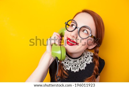 Redhead girl with green phone on yellow background. - stock photo
