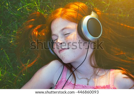 redhead girl with headphones listening to music dreaming - stock photo