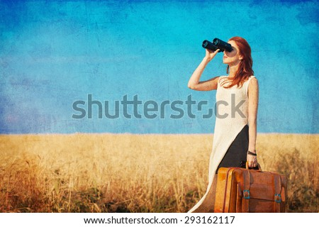 Redhead girl with suitcase and binocular at countryside road near wheat field. Photo in old color image style. - stock photo