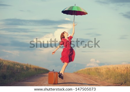 Redhead girl with umbrella and suitcase at outdoor - stock photo