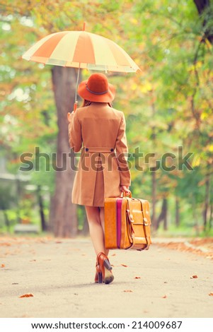Redhead girl with umbrella and suitcase in the autumn park. - stock photo