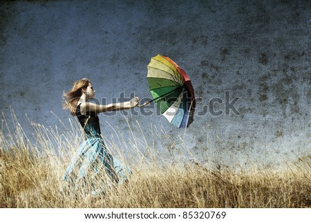 Redhead girl with umbrella at windy grass meadow. Photo in old color image style. - stock photo