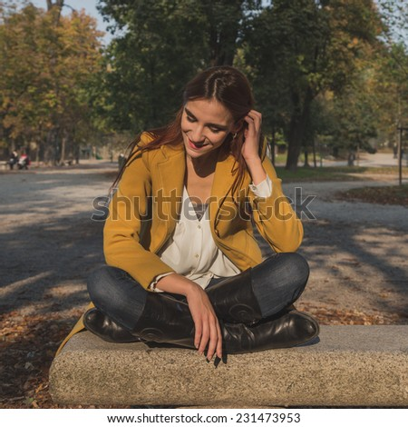 Redhead girl with yellow coat posing in a city park - stock photo