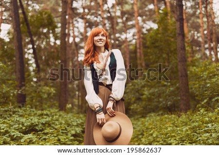 Redhead hippie walks in summer forest. Young woman with long hair in a long skirt and blouse in Boho style. Photo of romantic girl in national dress.  - stock photo