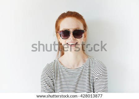 Redhead hipster teenage girl wearing sailor shirt and stylish sunglasses, looking and smiling at the camera with happy and cheerful expression against white concrete wall. People and lifestyle concept - stock photo