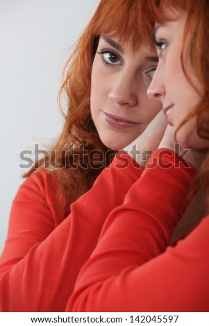 Redhead looking in a mirror - stock photo