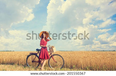 Redhead peasant girl with bicycle on wheat field. - stock photo