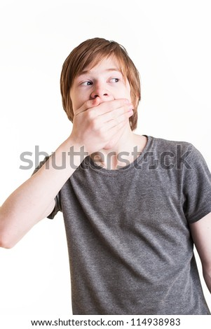 Redhead teen holding his mouth shut - stock photo