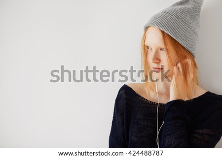 Redhead teenage girl wearing hipster cap listening to her favorite music with earphones. Pretty schoolgirl in headphones dancing against white background with copy space for your promotional content - stock photo