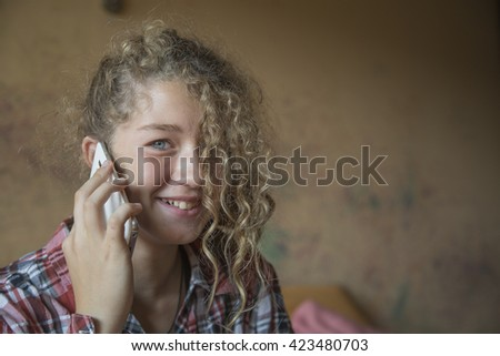 Redhead teenager talking on a mobile phone at home - stock photo