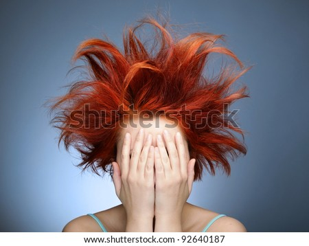 Redhead with messy hair covering her face with hands - stock photo