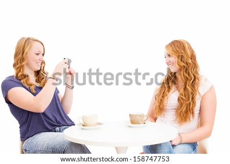 redhead woman making photos of her happy friend on white background - stock photo