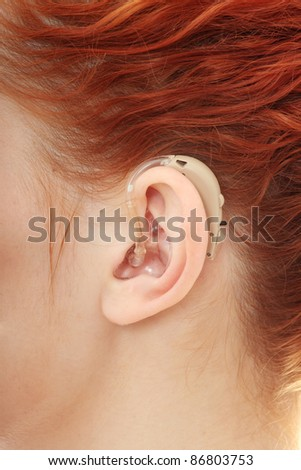 Redhead woman wearing hearing aid - stock photo