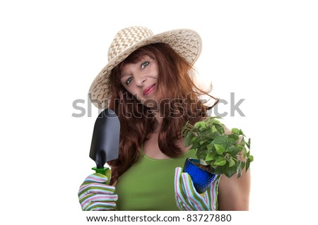 redhead woman working in the garden with straw hat - stock photo