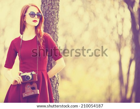 Redhead women  in a park with camera - stock photo