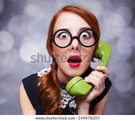 Redhead women with green telephone. - stock photo