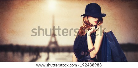 Redhead women with shopping bags on parisian background. - stock photo