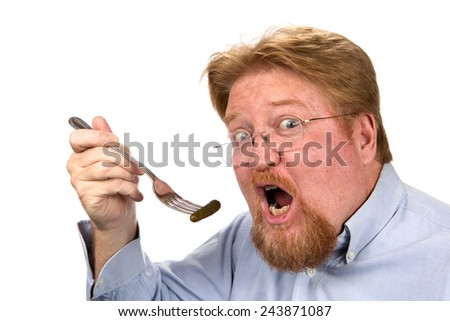 Redheaded mature man is about to eat a pickle impaled on a fork. - stock photo