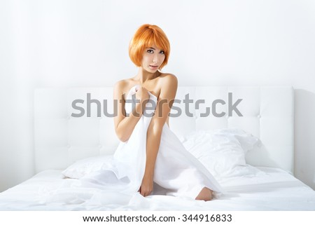 redheaded woman in  lingerie in the bedroom - stock photo